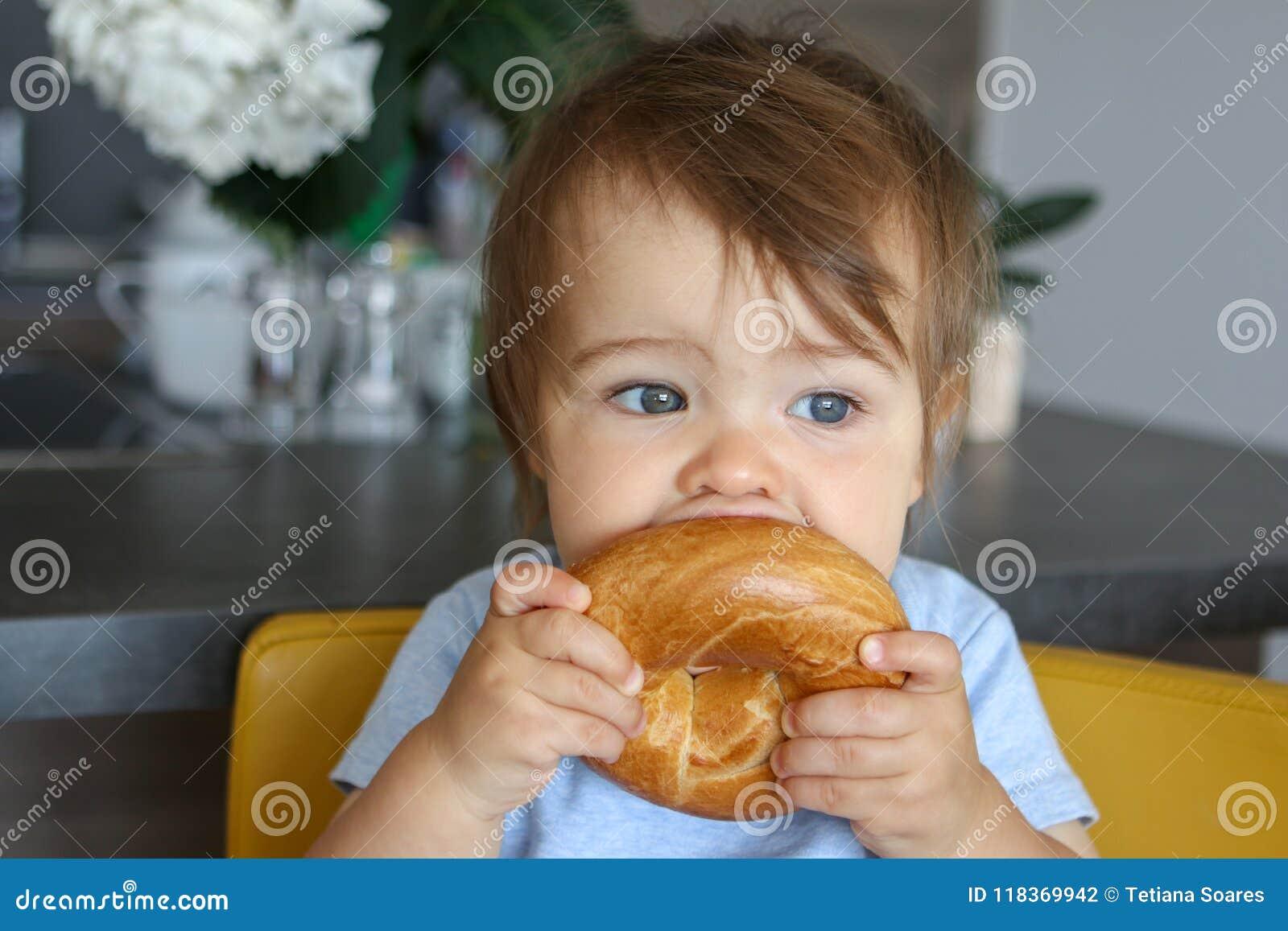 Portrait de se tenir drôle adorable de bébé garçon et du grand bagel acéré se reposant sur la cuisine jaune de chaise à la maison