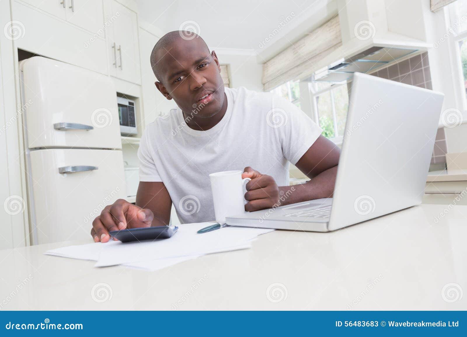 Portrait de son ordinateur portable et de regarder d homme d un fonctionnement et d à l aide l appareil-photo