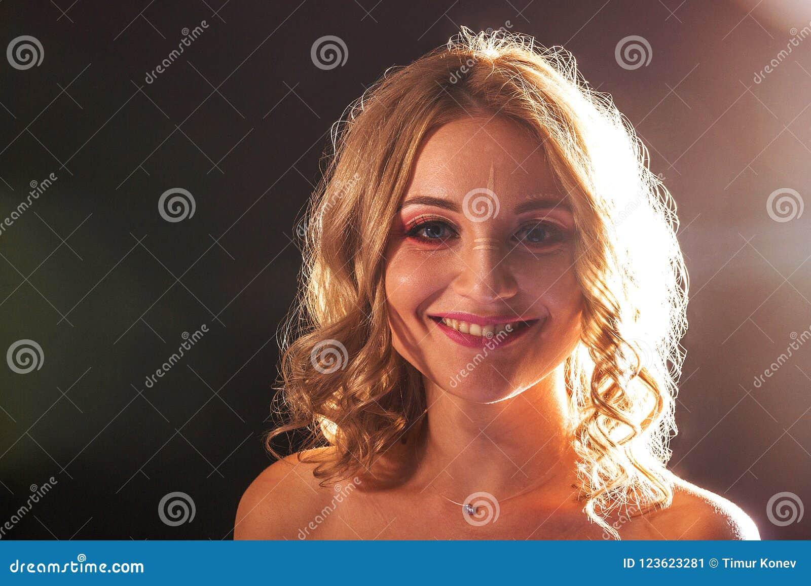 Portrait de studio Belle fille avec le maquillage de soirée sur un fond noir