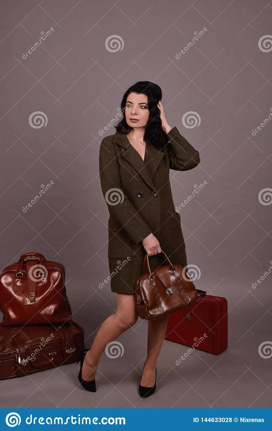 Portrait de studio d une femme dans le manteau classique posant avec l ensemble de rétros valises et de sac à main sur un fond