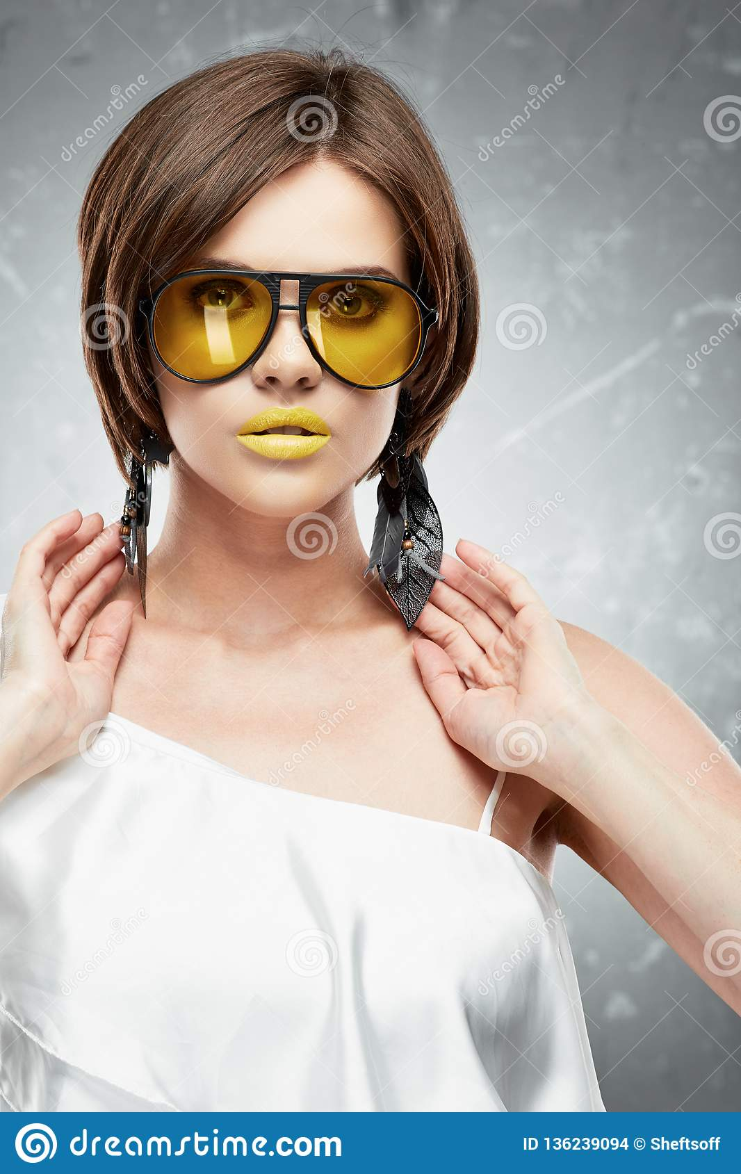 Portrait de visage de beauté de modèle avec les verres de soleil jaunes
