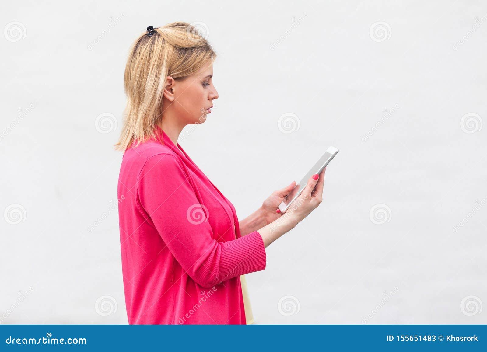 Portrait de vue de côté de jeune femme réfléchie de femme d affaires dans la position rose de chemisier, utilisant le comprimé à