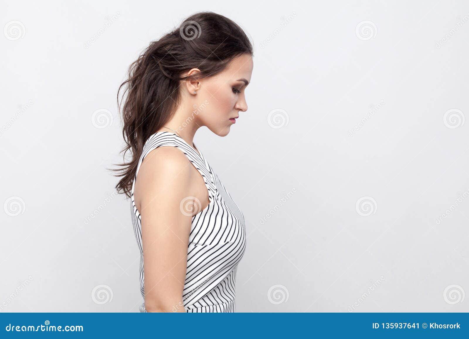 Portrait de vue de côté de profil de belle jeune femme triste de brune avec le maquillage et de chef rayé de participation de pos