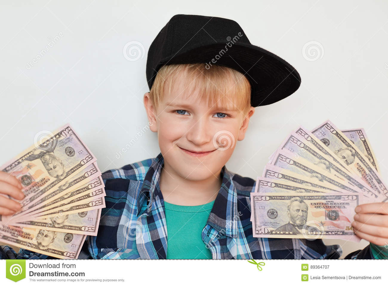 A portrait of delighted little stylish boy in black cap holding money in his hands. A happy child male holding cash isolated over