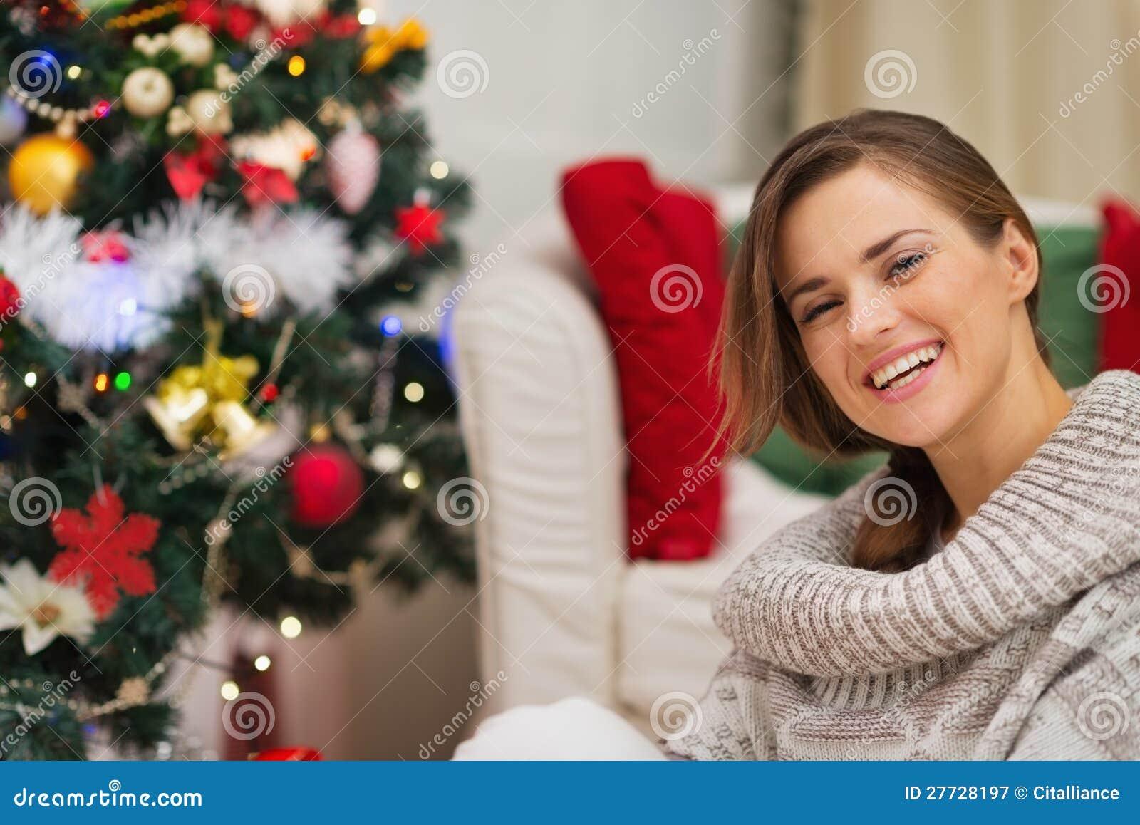 Portrait der glücklichen Frau nahe Weihnachtsbaum