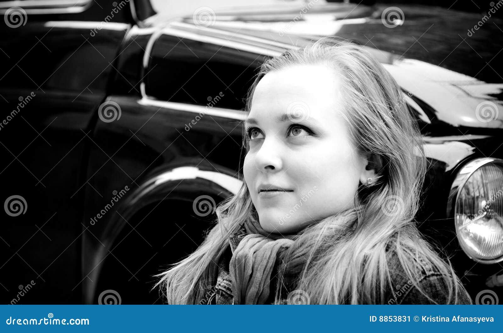 Portrait der jungen Frau sitzend gegen Retro- Auto