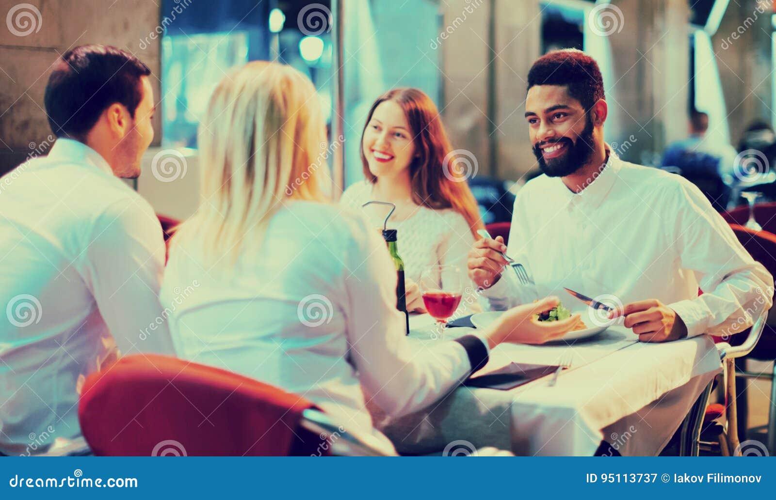 Portrait des adultes heureux et souriants dînant