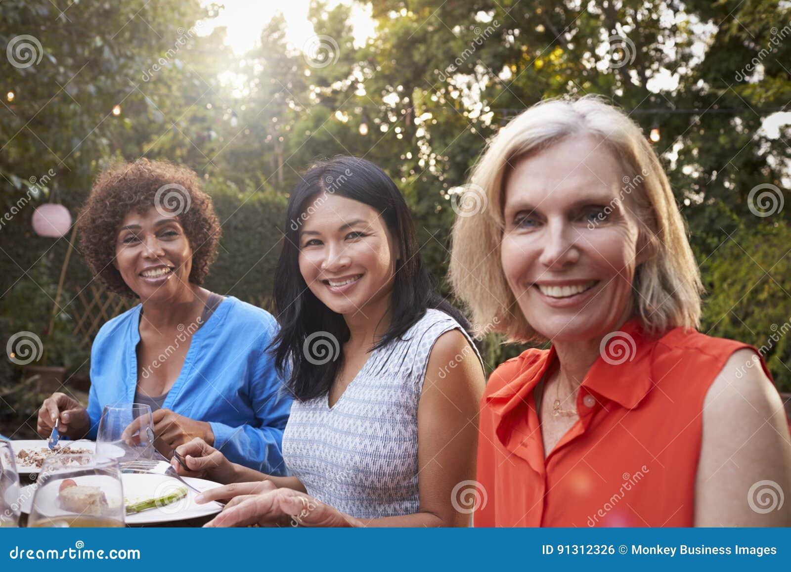 Portrait des amis féminins mûrs appréciant le repas extérieur