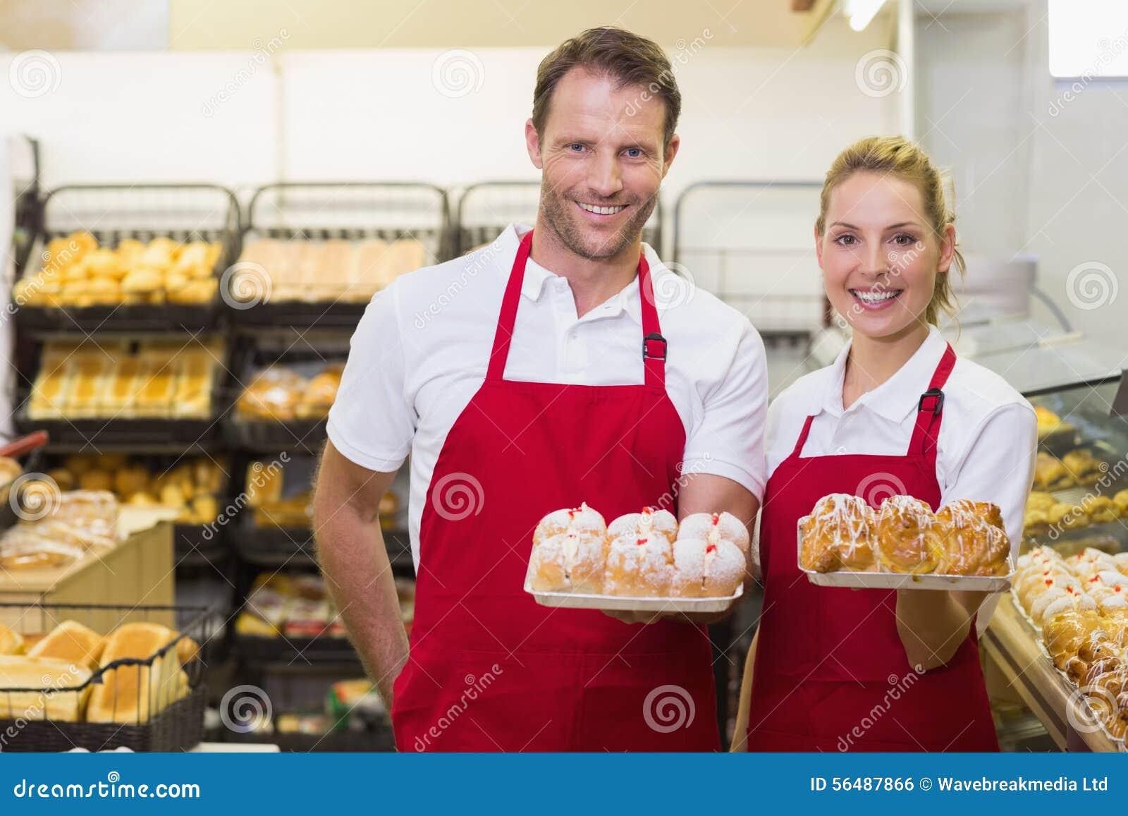 Portrait des boulangers de sourire ayant une pâtisserie