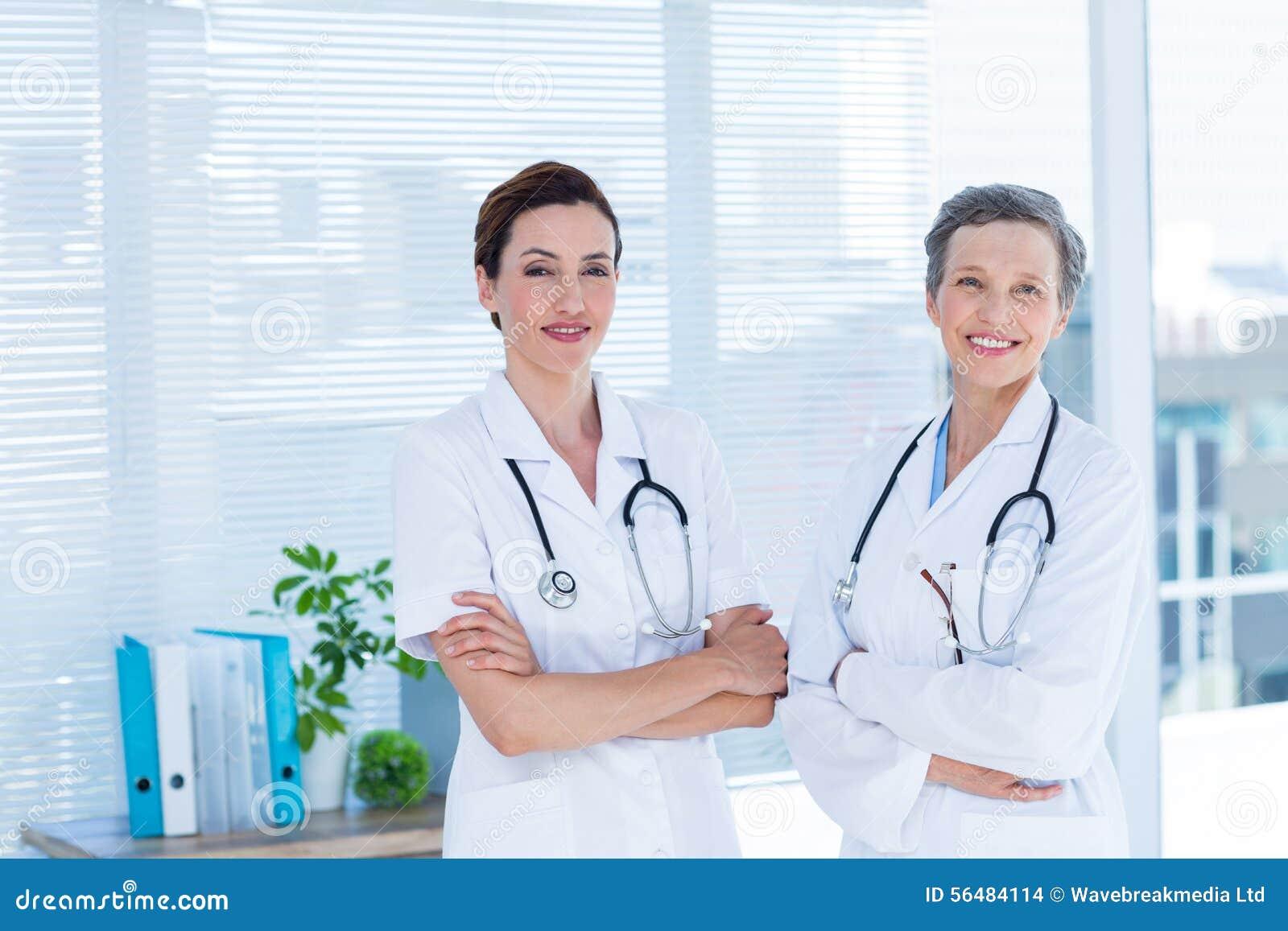 Portrait des collègues médicaux de sourire avec des bras croisés