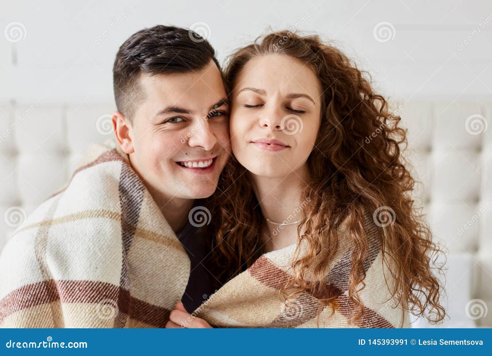 Portrait des couples heureux mignons se reposant dans le lit pour s embrasser La belle fille avec de longs cheveux bouclés s ass