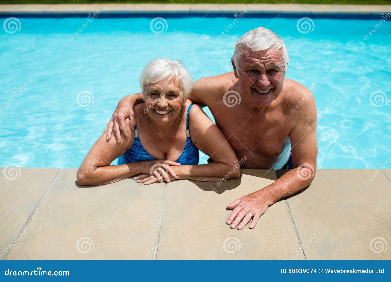 Portrait des couples supérieurs détendant ensemble dans la piscine