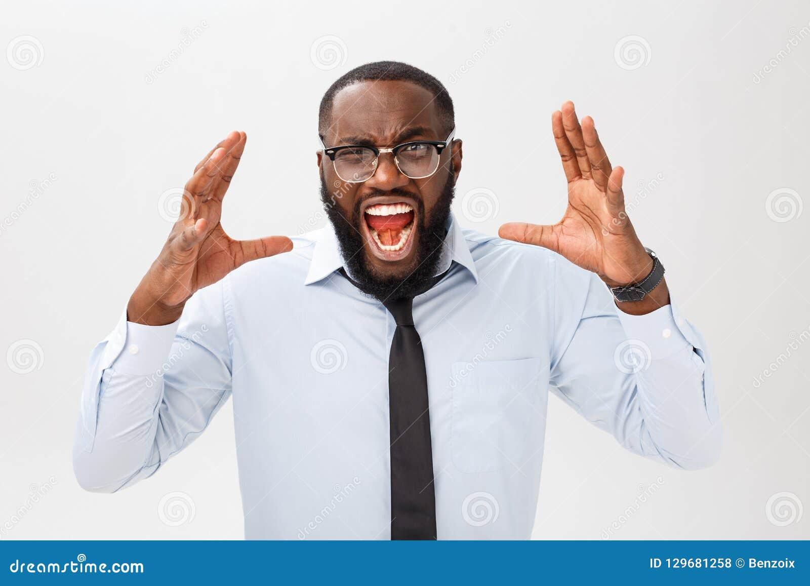 Portrait des cris masculins noirs contrariés désespérés dans la rage et la colère arrachant ses cheveux tout en se sentant furieu