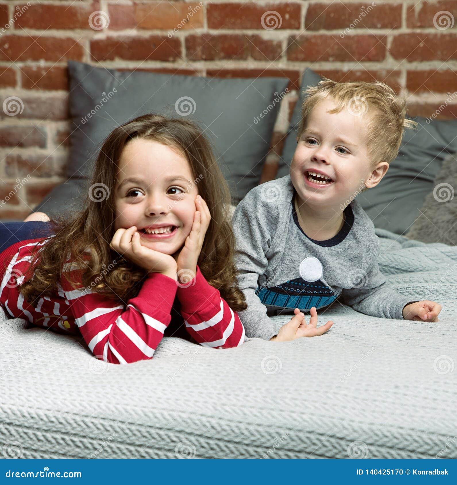 Portrait des enfants de mêmes parents gais détendant dans la chambre à coucher