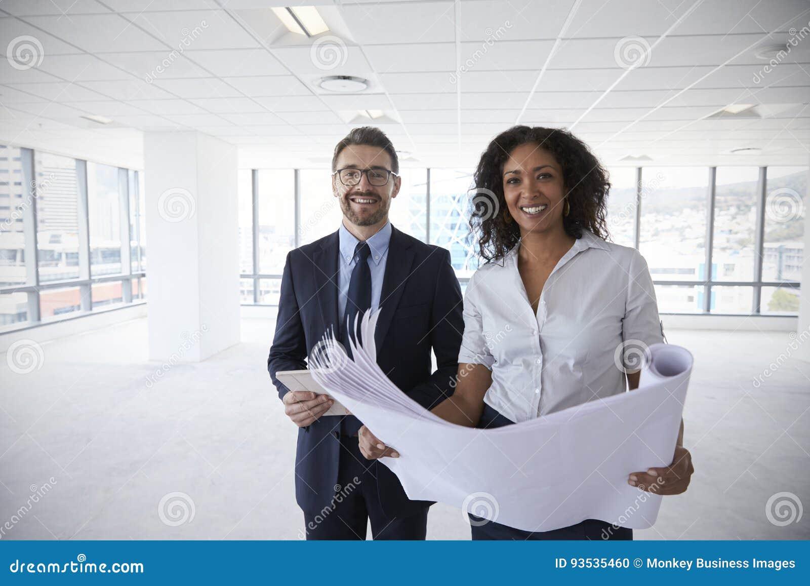 Portrait des hommes d affaires regardant des plans dans le bureau vide
