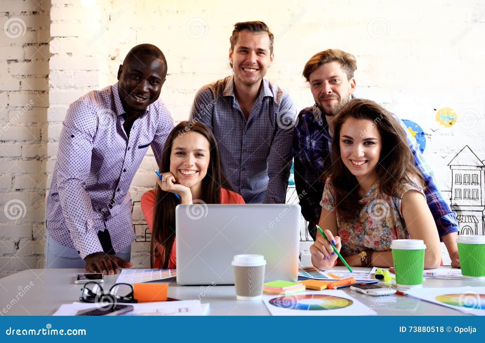 Portrait des jeunes heureux lors d une réunion regardant l appareil-photo et le sourire Jeunes concepteurs travaillant ensemble s