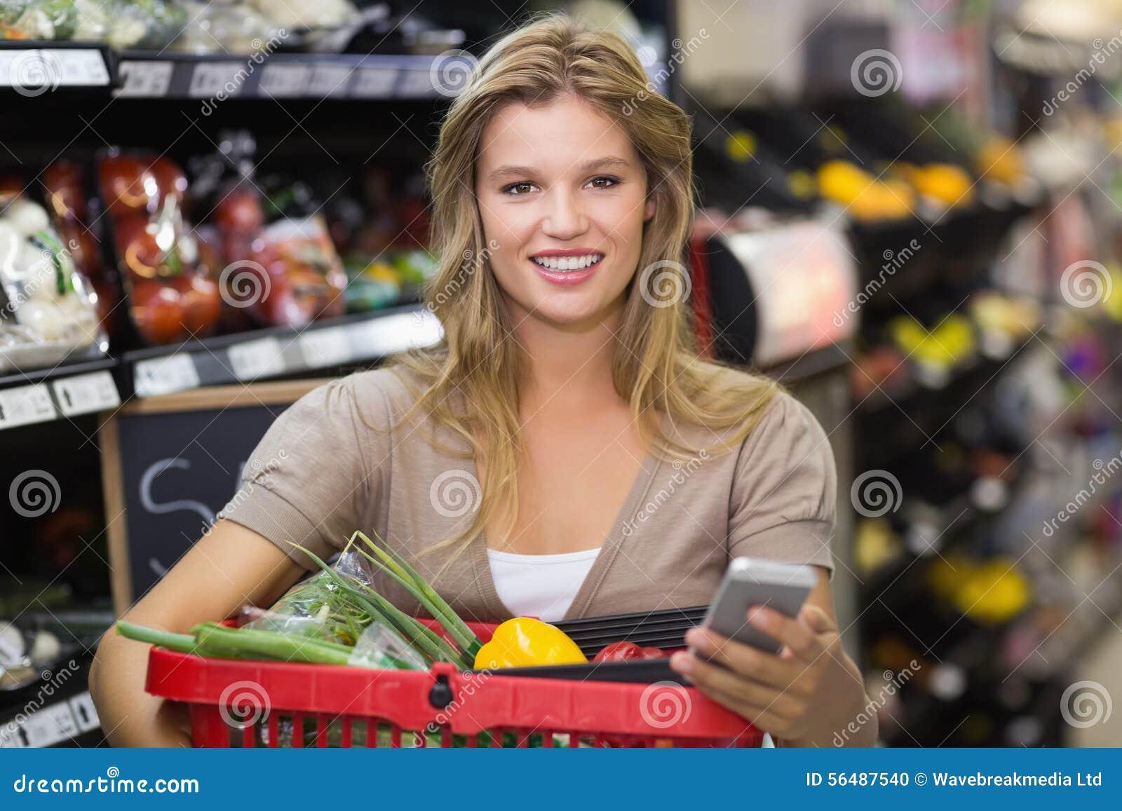 Portrait des légumes de achat de sourire et d à l aide de femme blonde de son smartphone