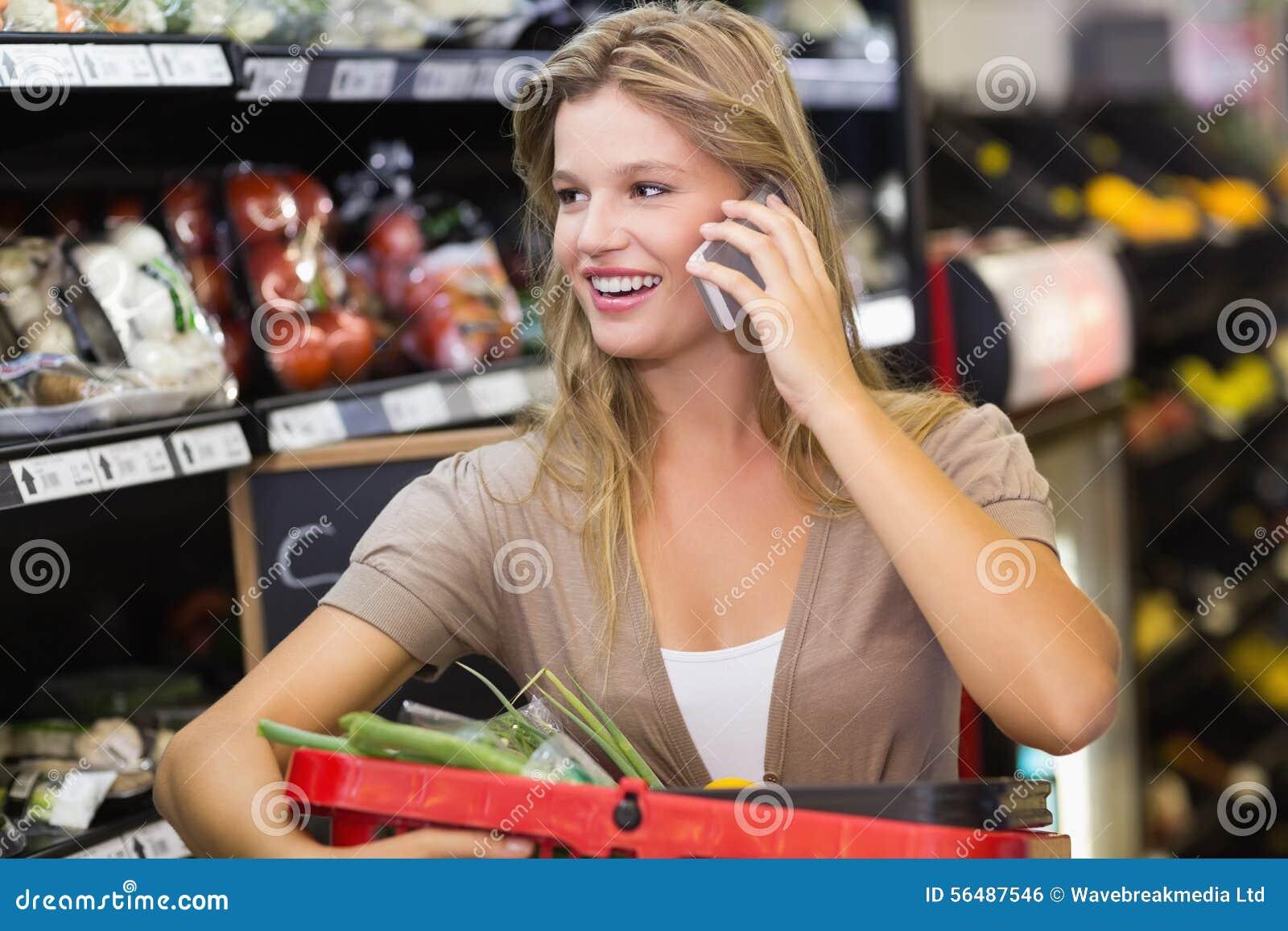 Portrait des légumes de achat de sourire et de téléphoner de femme blonde