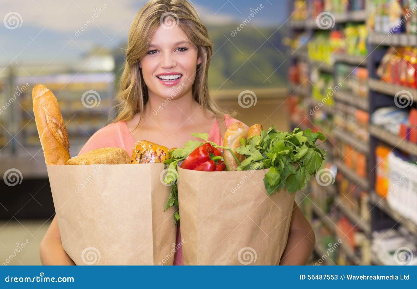 Portrait des produits alimentaires de achat de femme assez blonde