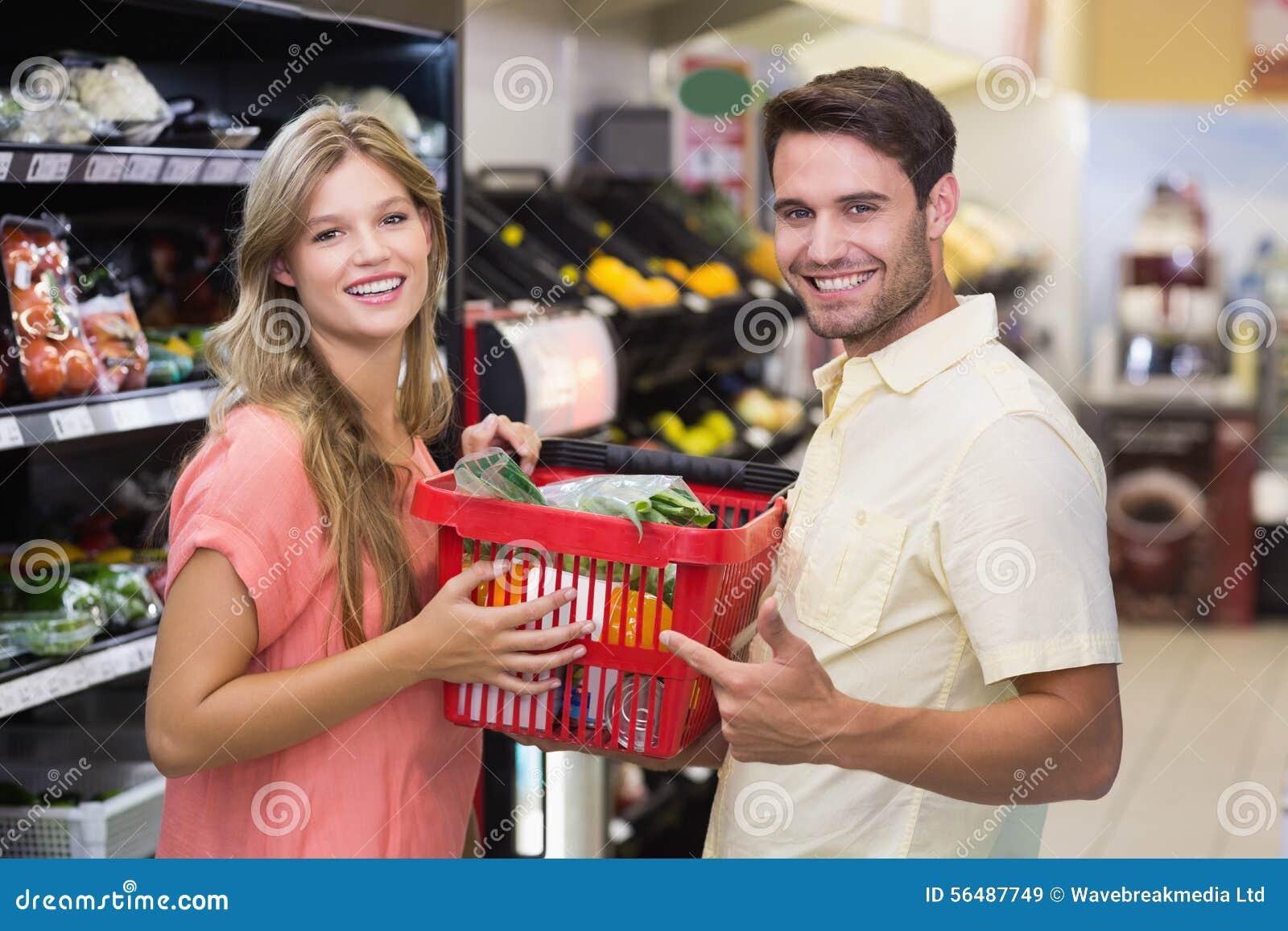 Portrait des produits alimentaires de achat de sourire de couples lumineux