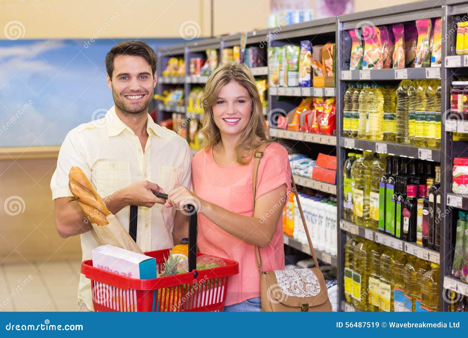 Portrait des produits alimentaires de achat de sourire de couples lumineux utilisant le panier à provisions