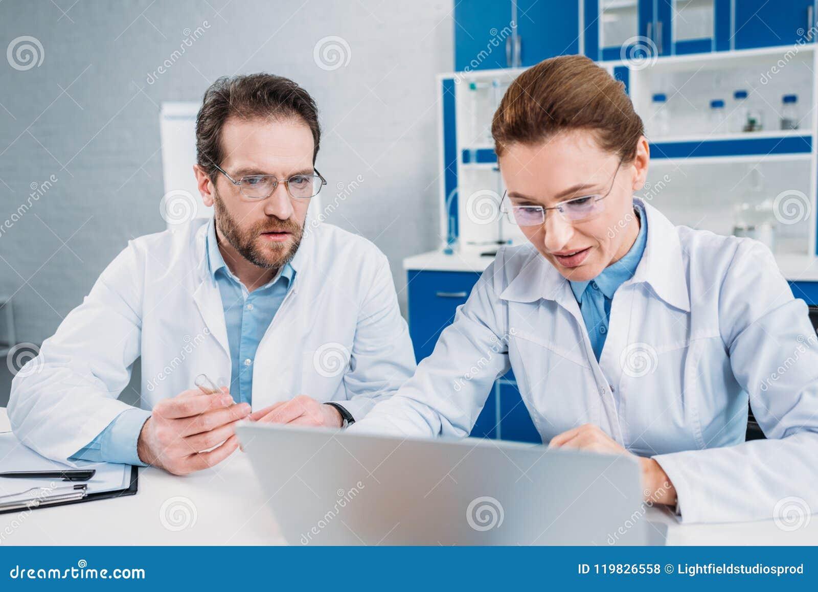 Portrait des scientifiques dans des manteaux et des lunettes de laboratoire travaillant sur l ordinateur portable ensemble sur le
