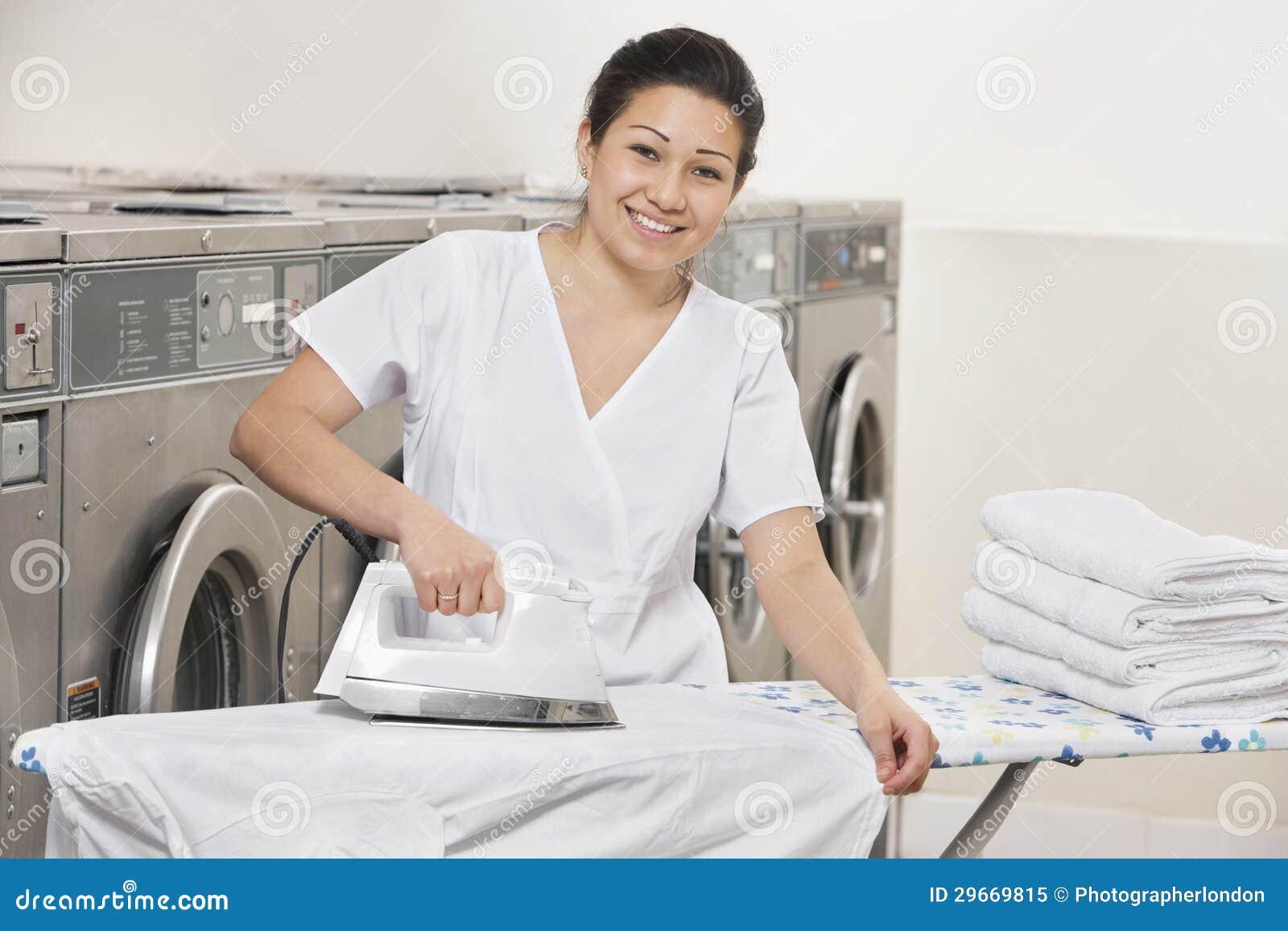 Portrait des vêtements repassants d une jeune femme heureuse dans la laverie automatique