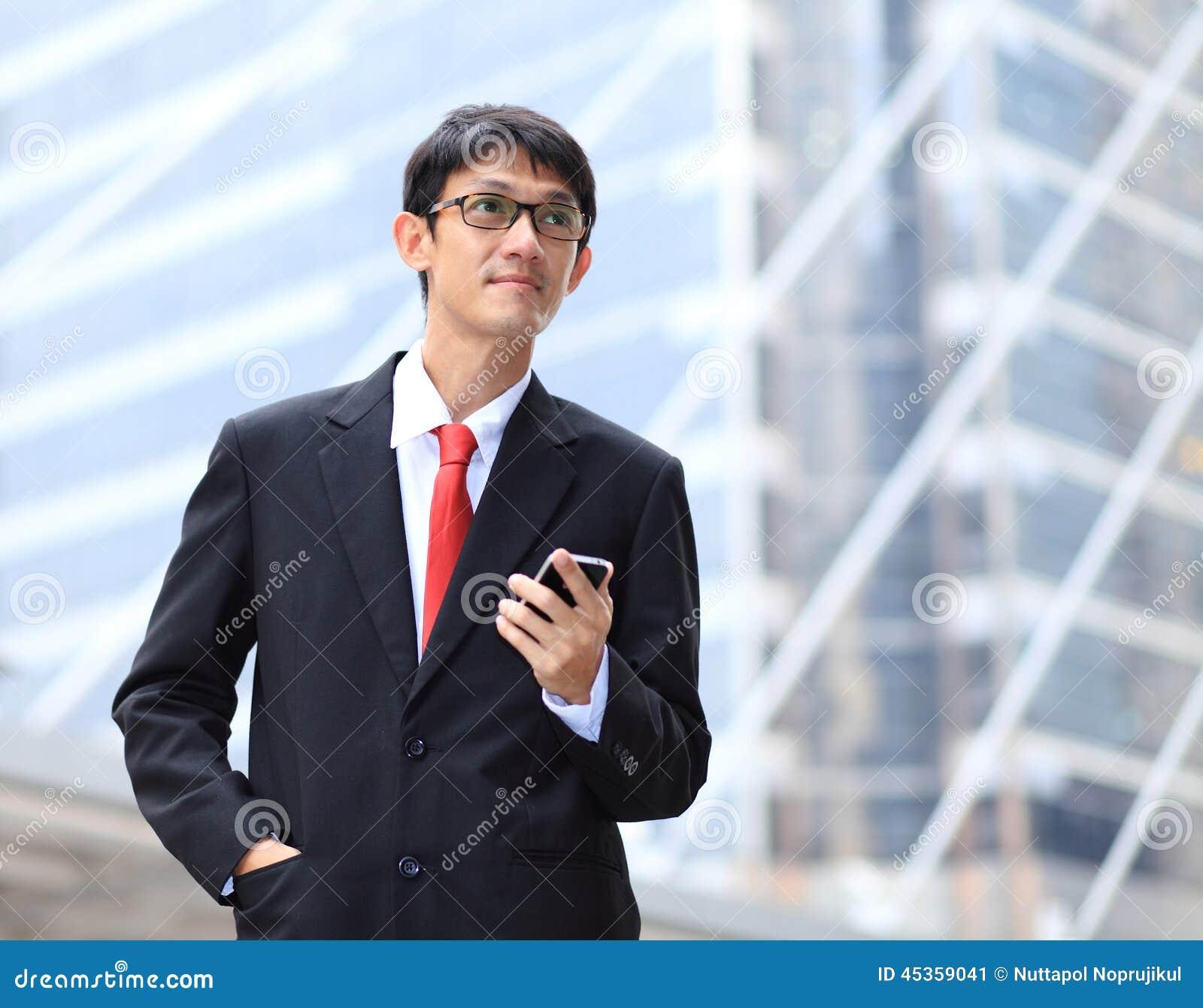 Portrait des verres de jeune homme d affaires et du smartpho de port d utilisation