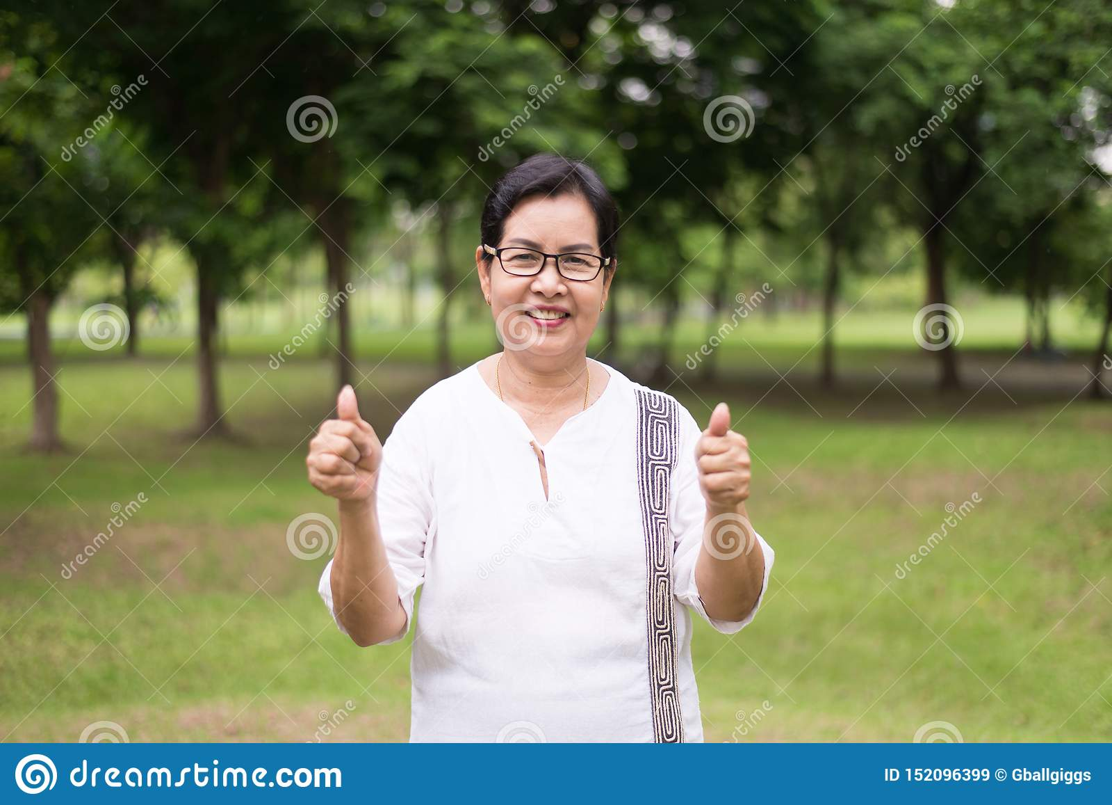 Portrait des verres de port de femme asiatique pluse âgé montrant le pouce au parc public, heureux et souriant, pensée d attitude