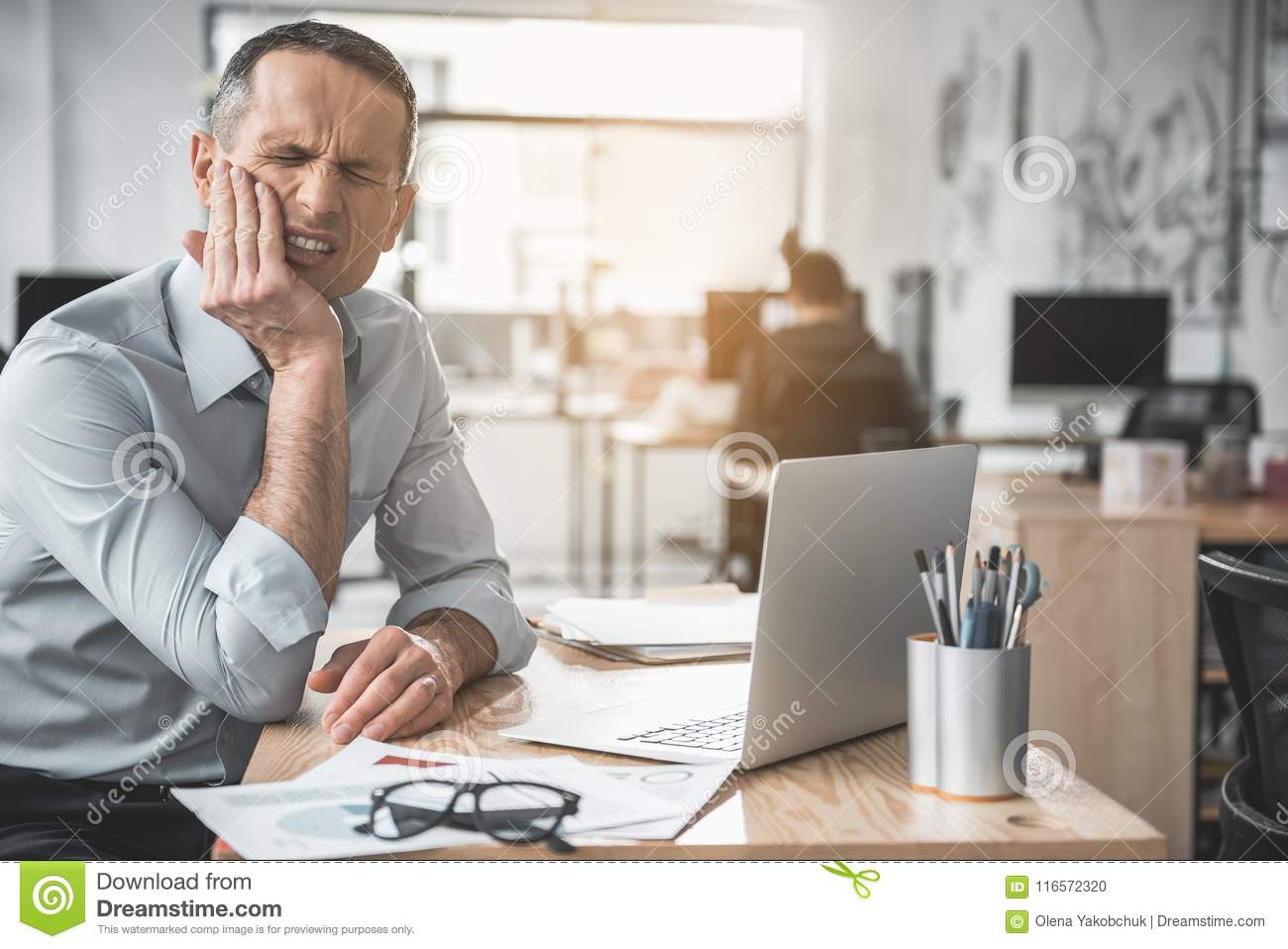 Disillusioned male having toothache at job