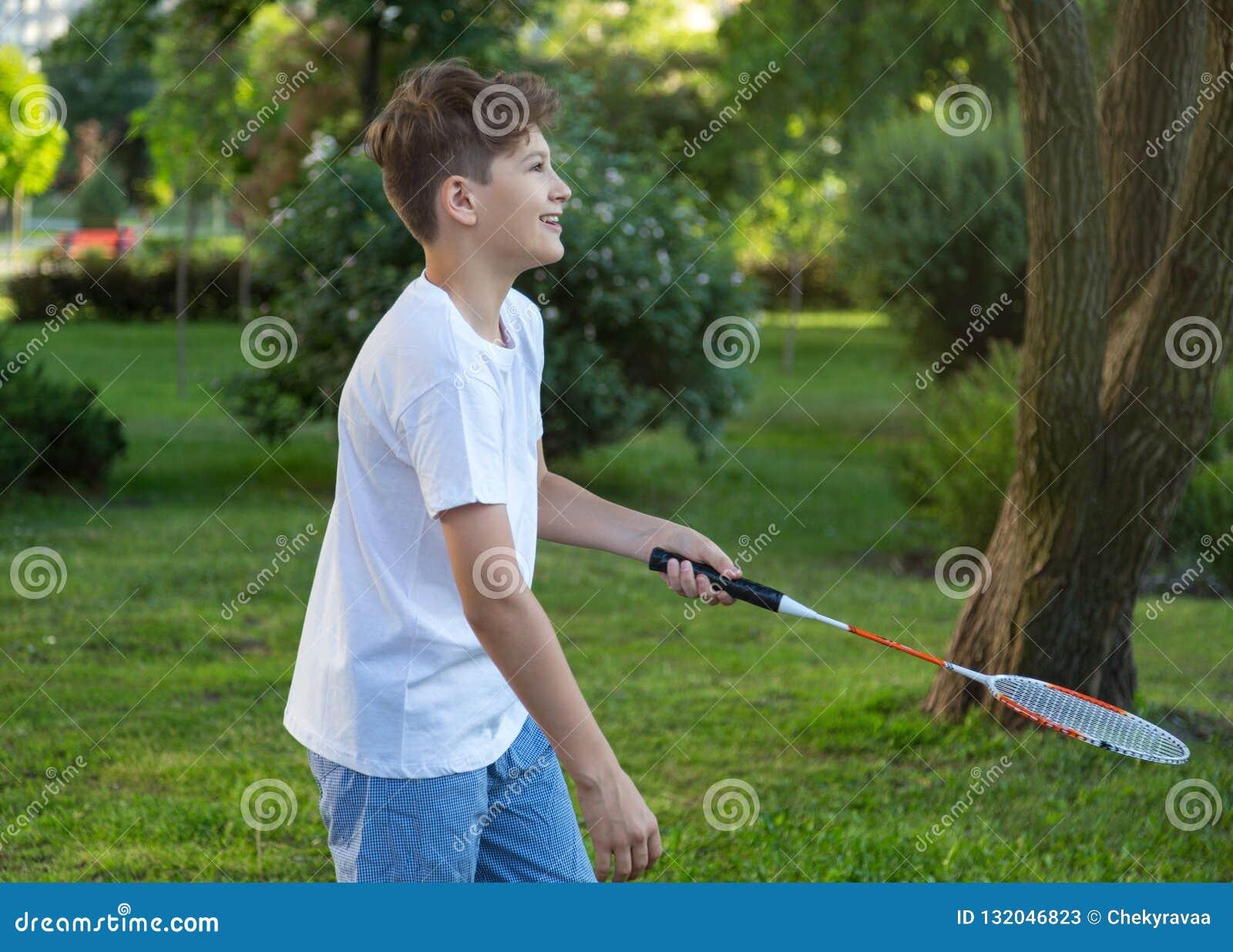 Portrait drôle d été de l enfant mignon de garçon jouant au badminton en parc vert Style de vie sain