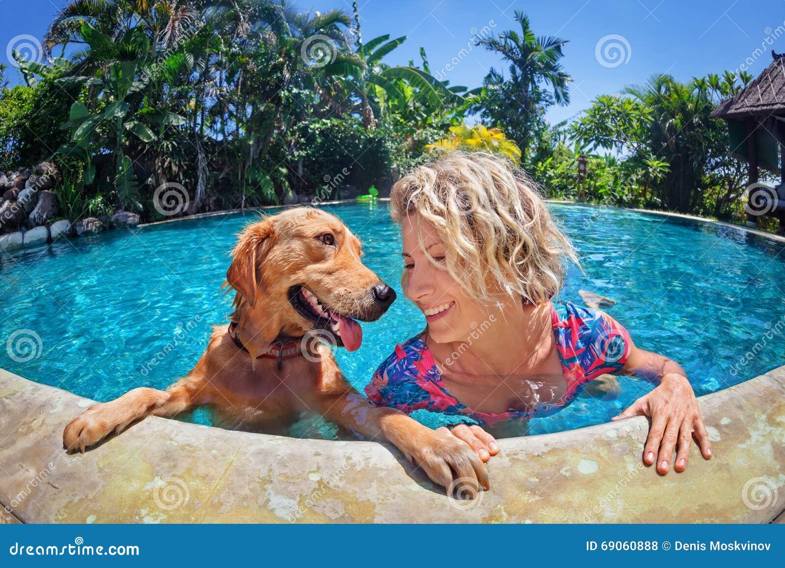 Portrait drôle de femme souriante avec le chien dans la piscine
