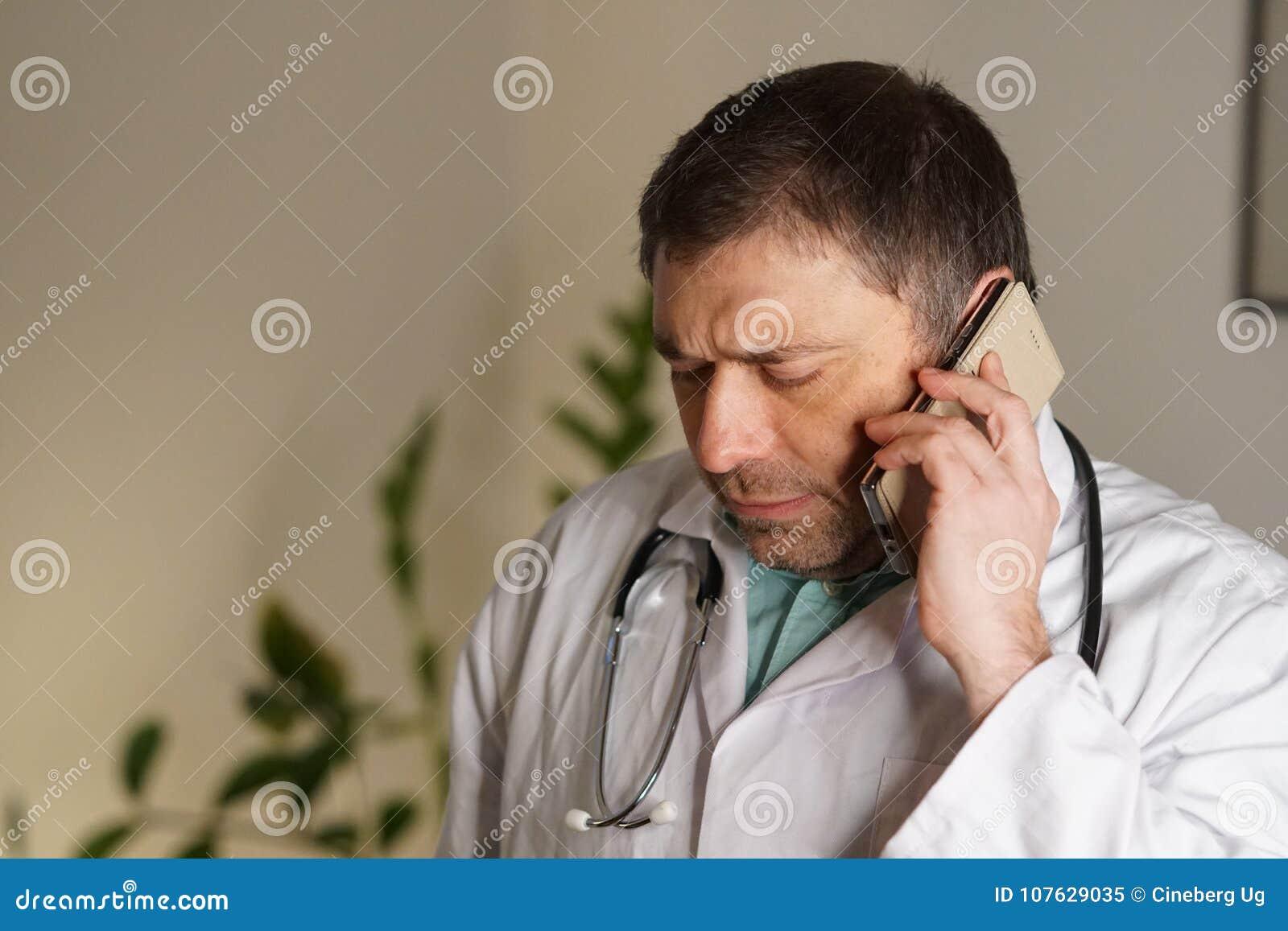 Portrait du docteur absorbé parlant à son téléphone portable