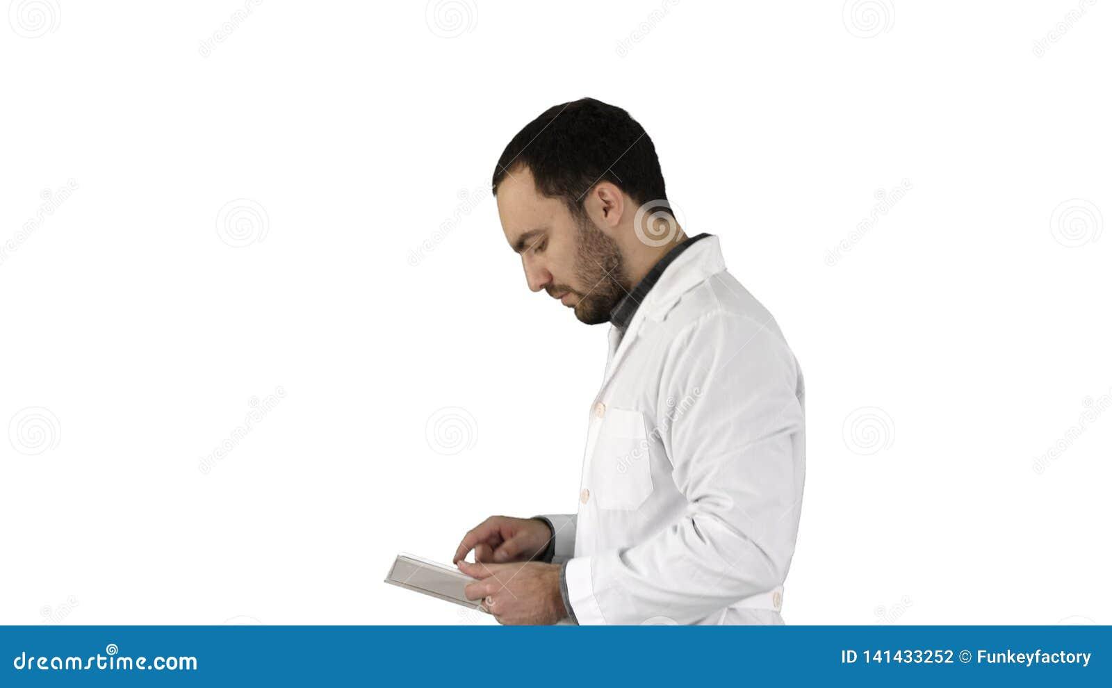Portrait du docteur masculin marchant et à l aide du comprimé numérique sur le fond blanc