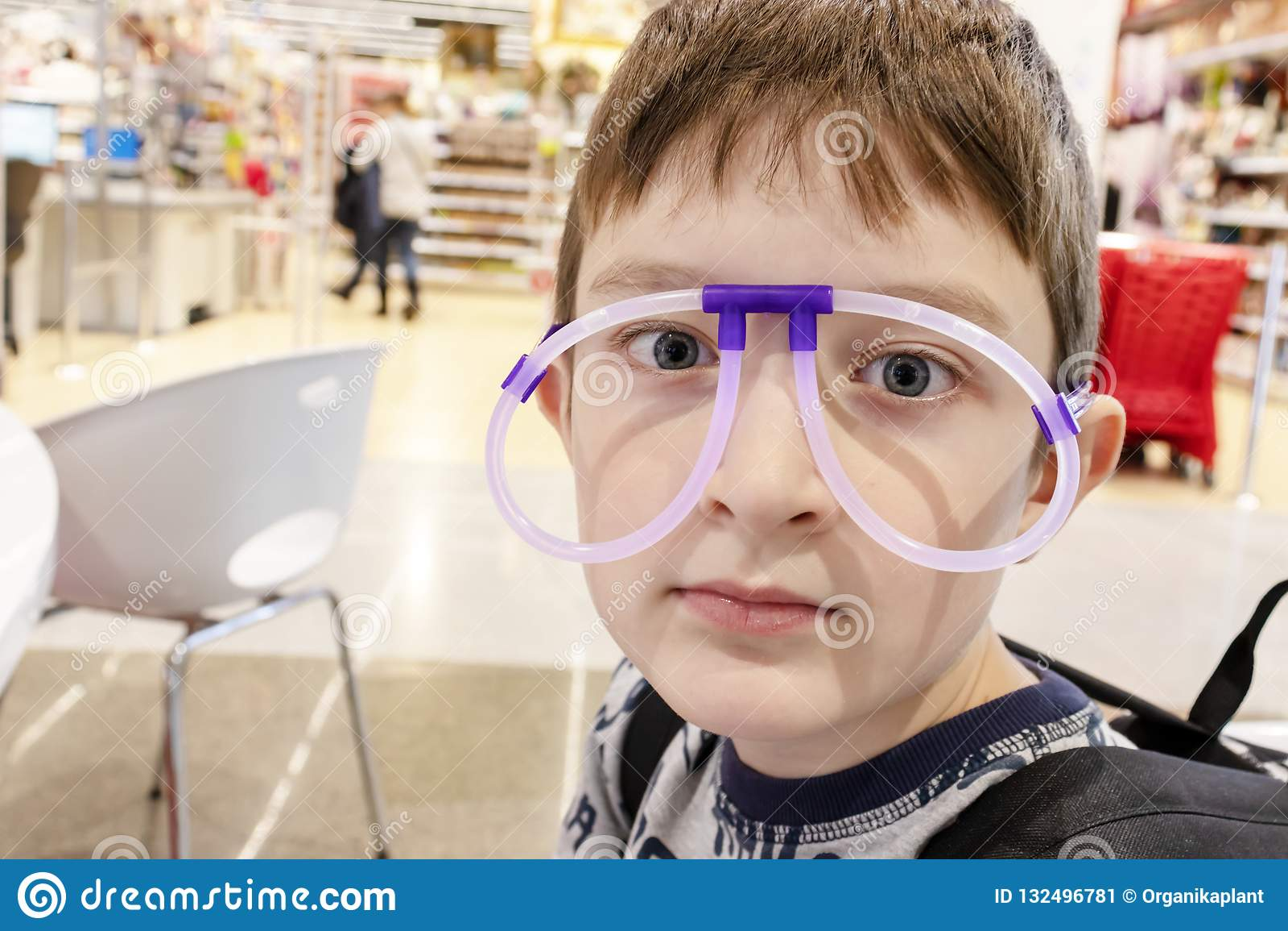 Portrait du garçon mignon drôle portant les lunettes étranges faites de tubes au néon fluorescents, centre commercial