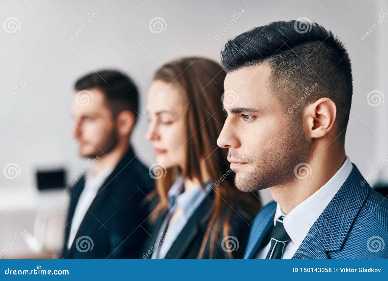 Portrait du groupe de jeunes hommes d affaires dans une rangée dans le bureau