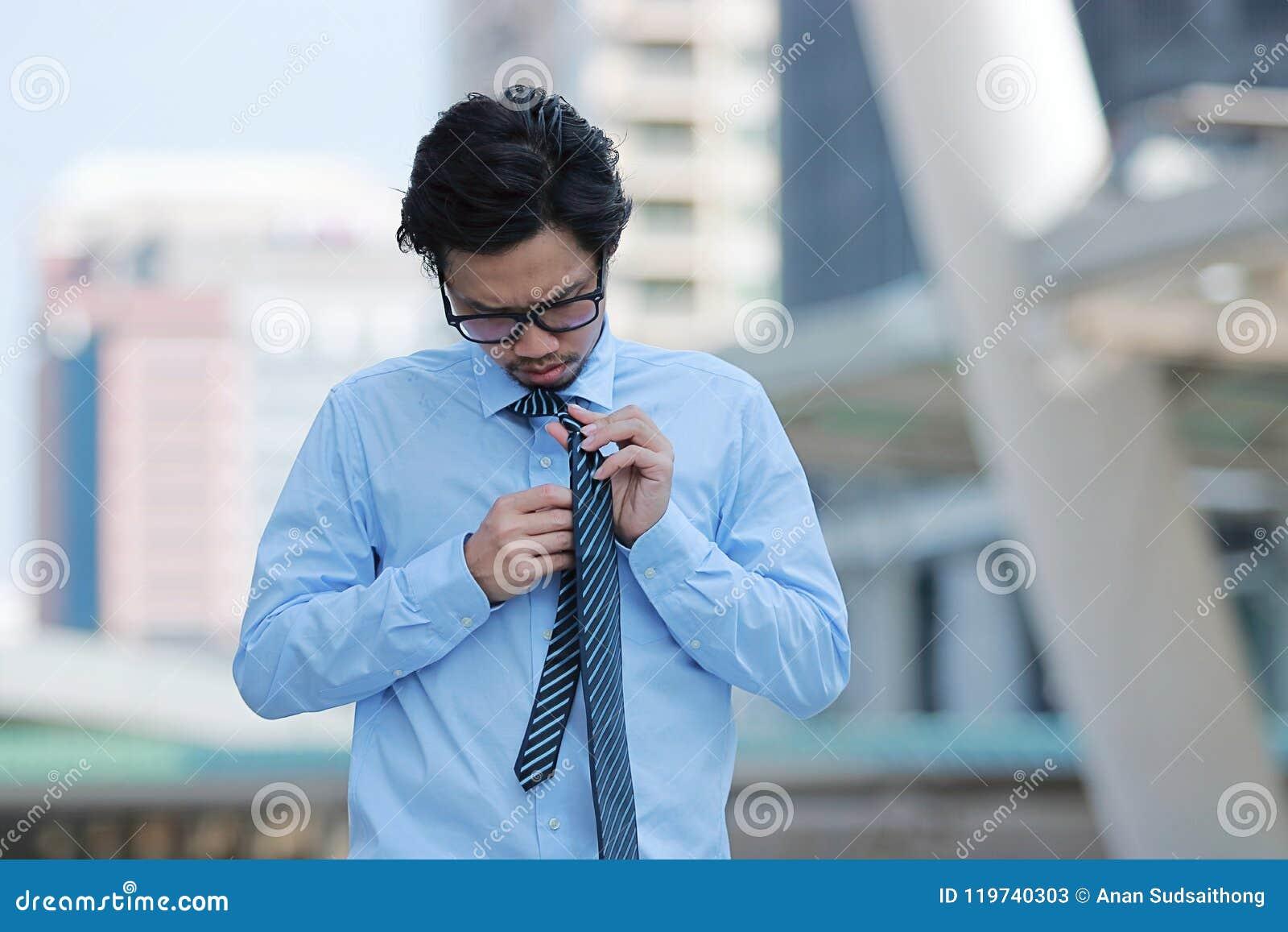 Portrait du jeune homme asiatique soumis à une contrainte d affaires liant le lien sur le bâtiment urbain à l arrière-plan de vil
