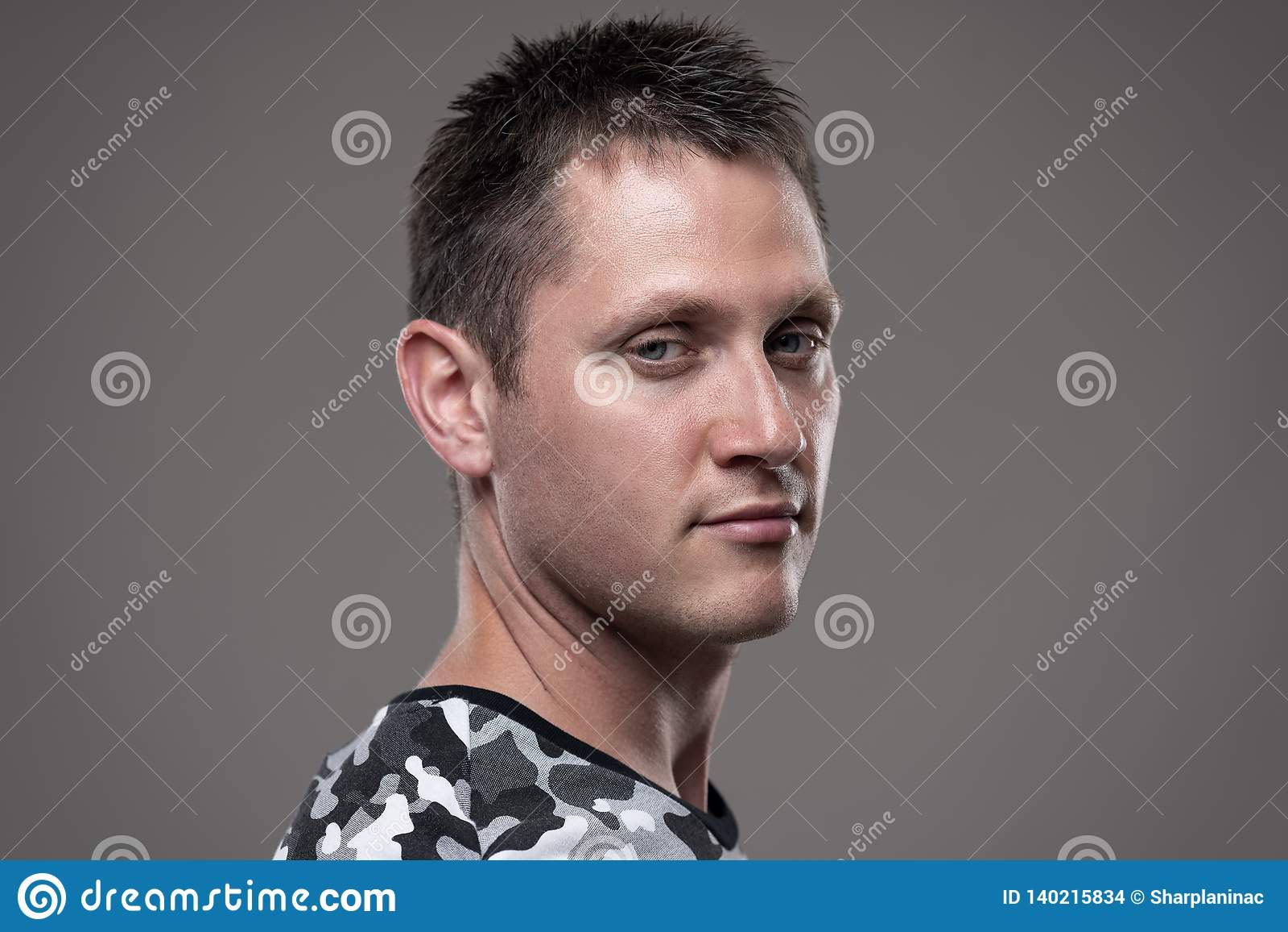 Portrait du jeune homme frais indifférent regardant la caméra avec l expression sceptique