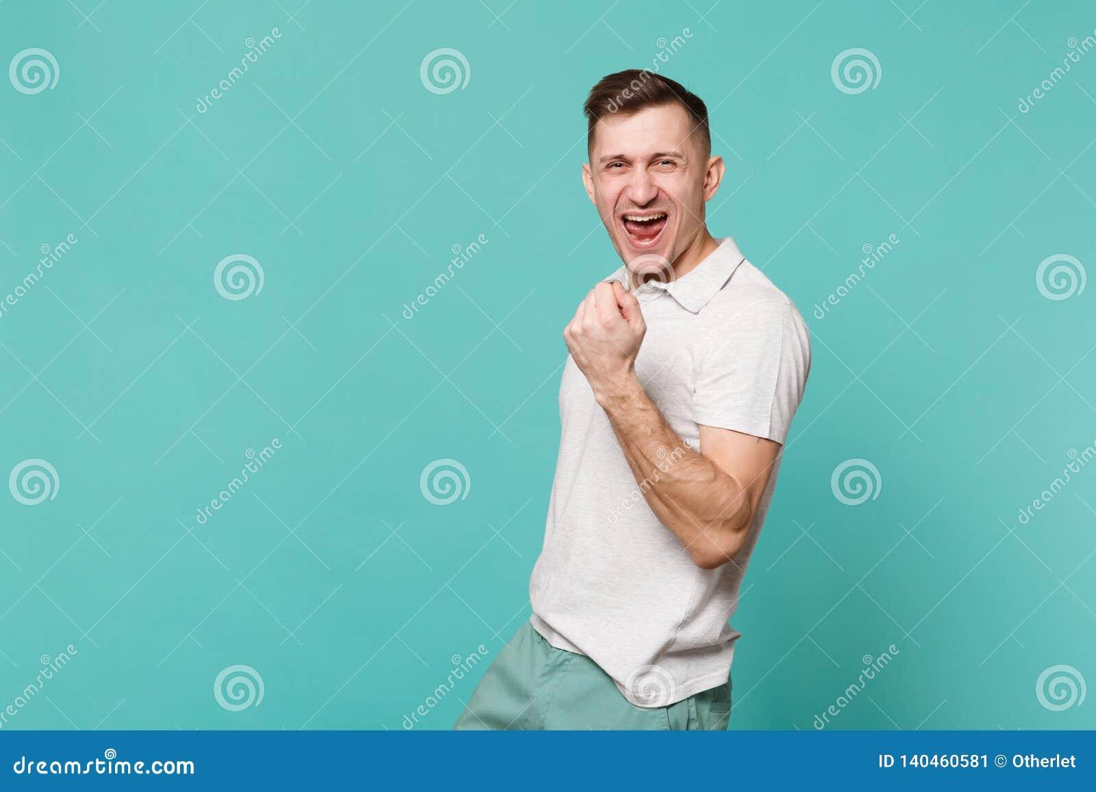 Portrait du jeune homme riant joyeux dans des vêtements sport se tenant, faisant le geste de gagnant d isolement sur la turquoise