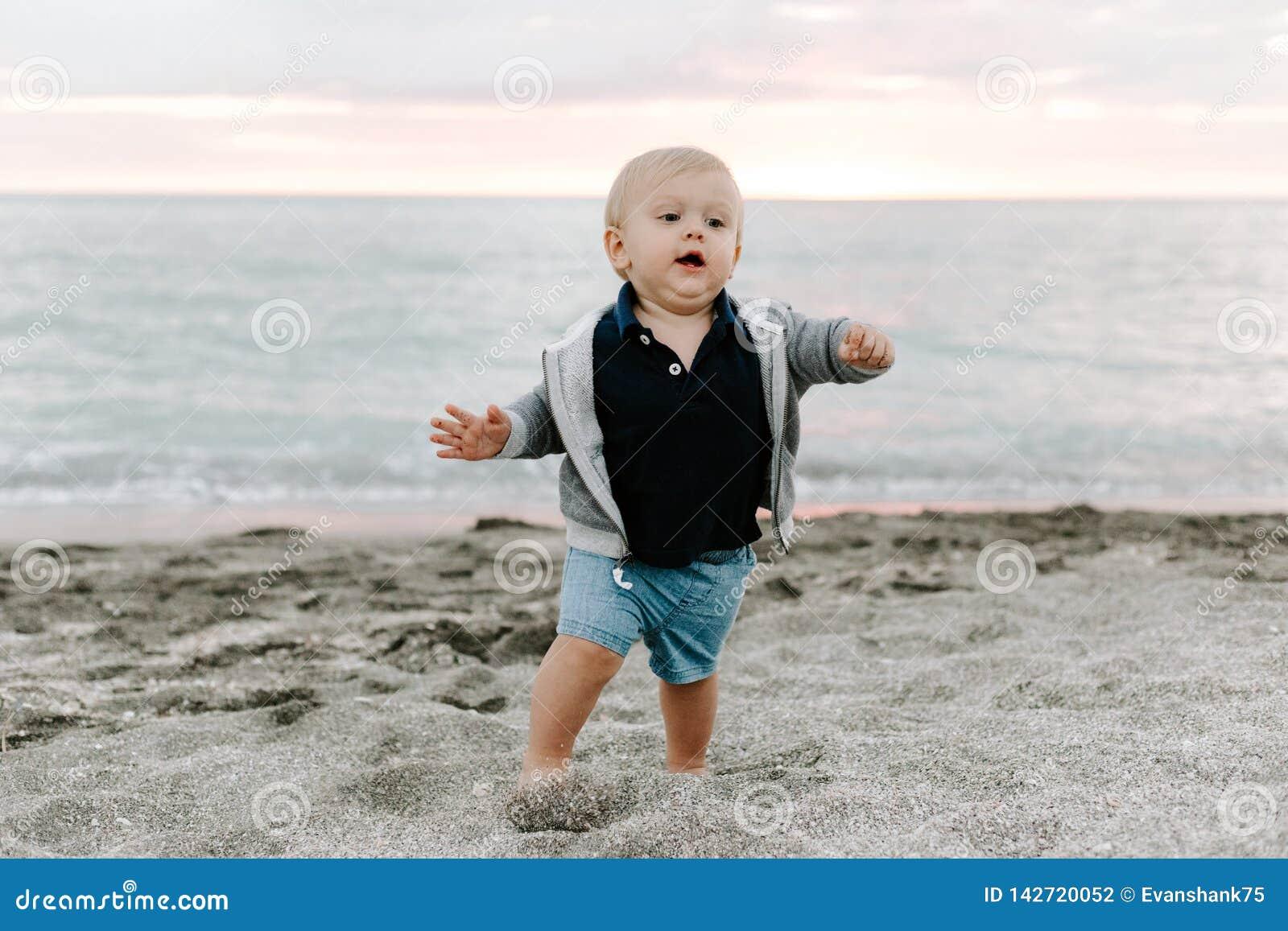 Portrait du petit enfant mignon de bébé garçon jouant et explorant dans le sable à la plage pendant l extérieur de coucher du sol