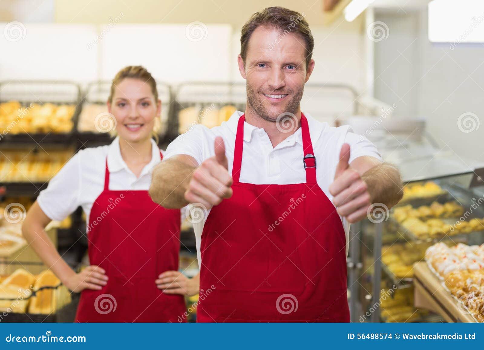 Portrait du sourire deux boulangers avec le pouce