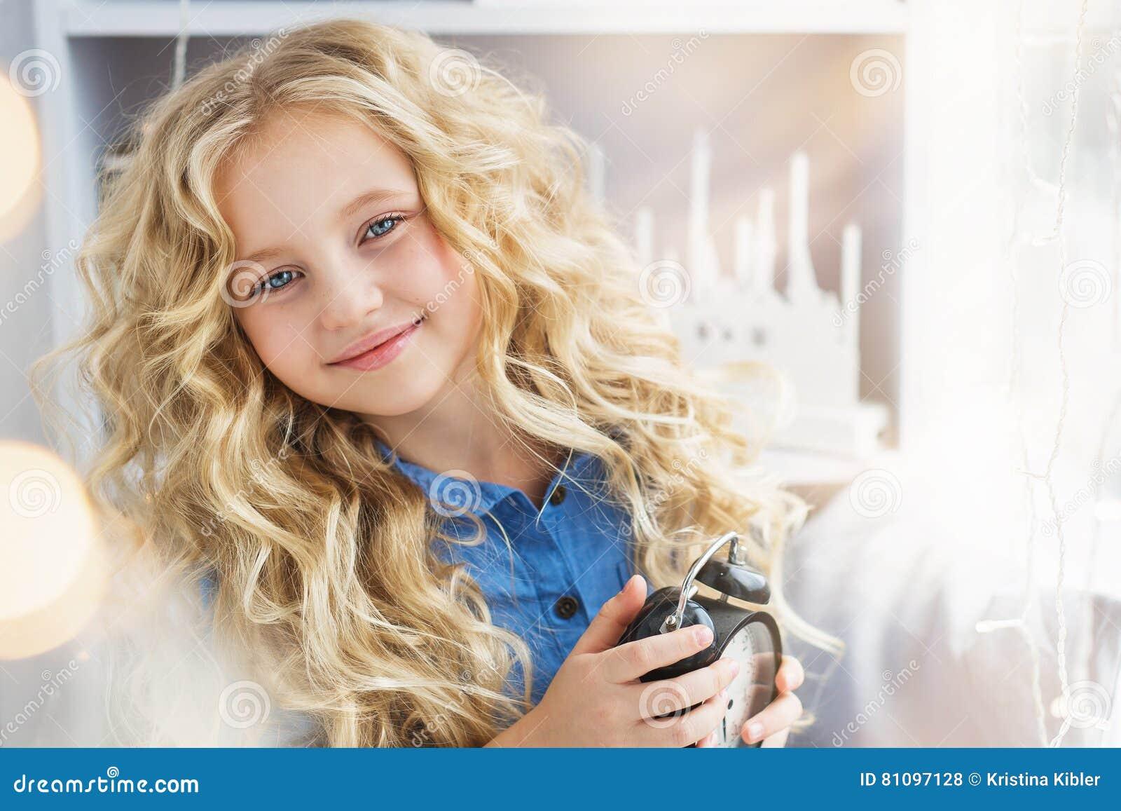 Portrait du sourire fille assez petite avec une horloge aux mains près de la fenêtre