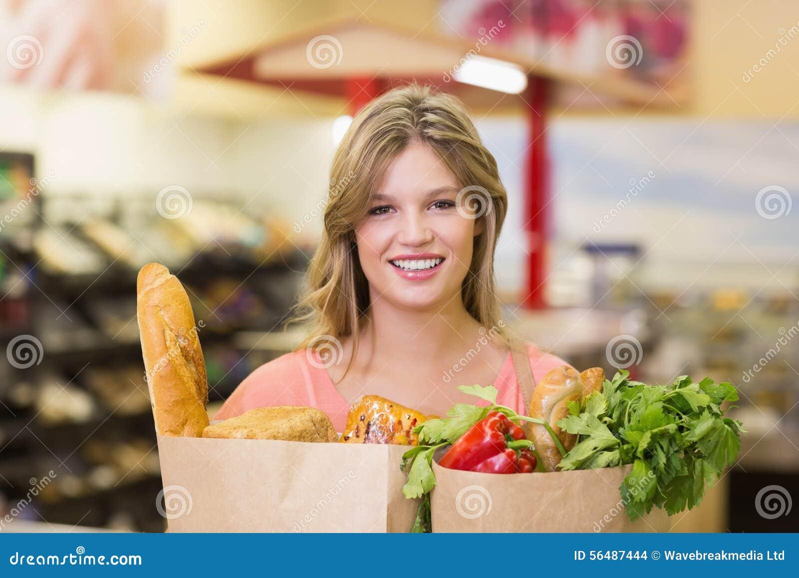 Portrait du sourire produits alimentaires de achat de femme assez blonde