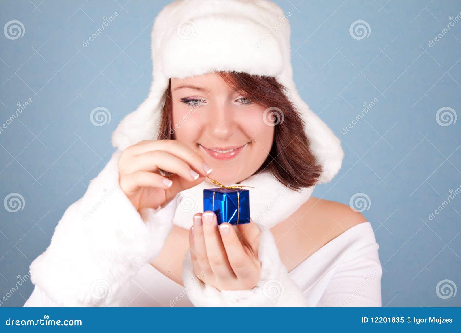 Portrait eines Mädchens im weißen Hut, der ein Geschenk öffnet