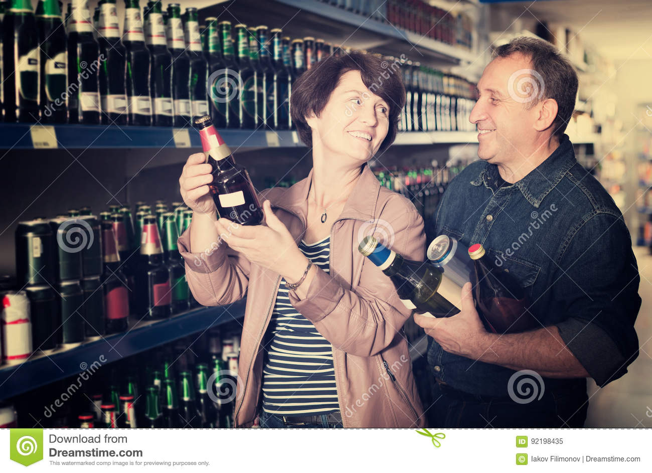 Portrait of an elderly couple buying a beer at the grocery store