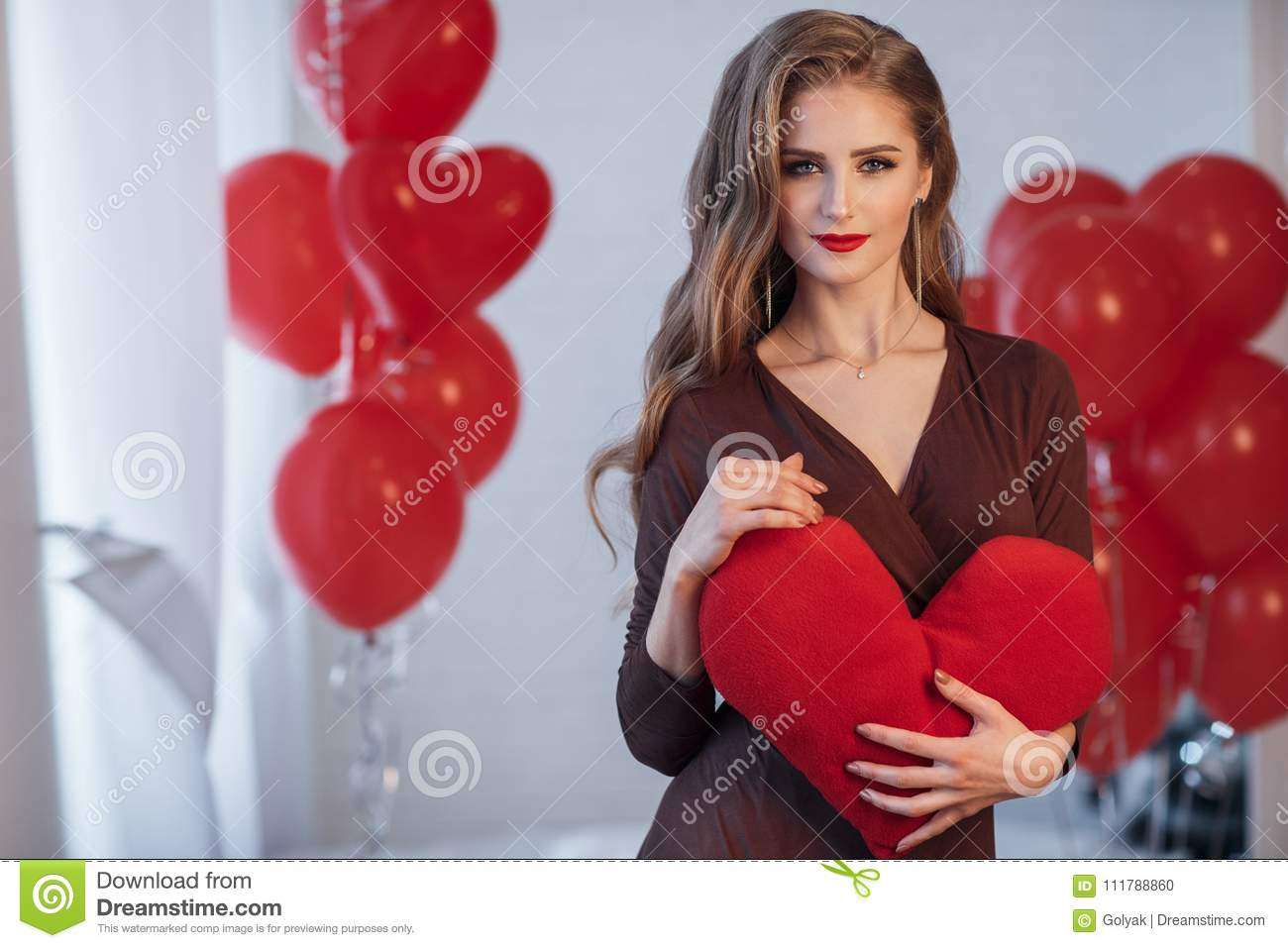 Portrait of a beautiful woman in valentine`s day on a background of red air balloons