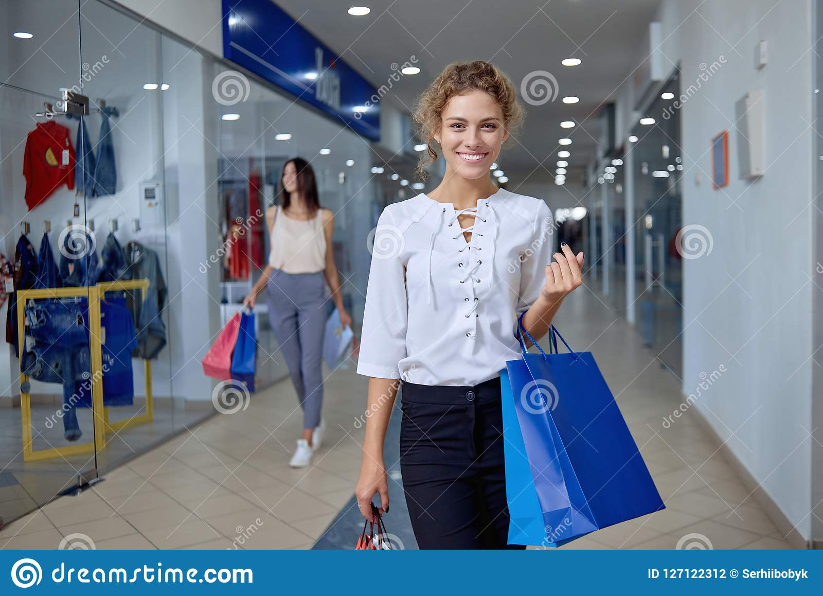 6db90afe Portrait of elegant women in white shirt and black trousers with bags  shopping in mall. Curly blonde going in hallway, looking at camera and  smiling.