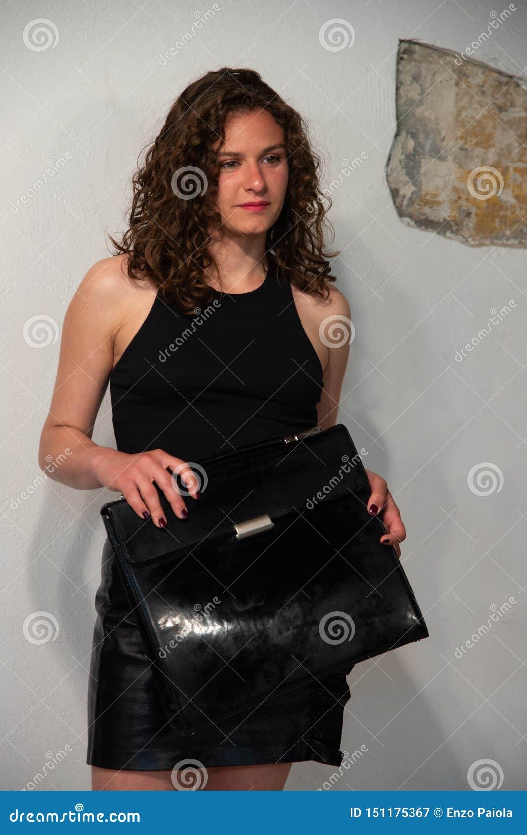 Portrait en buste de jeune femme bouclée de brune avec la serviette noire dans sa main