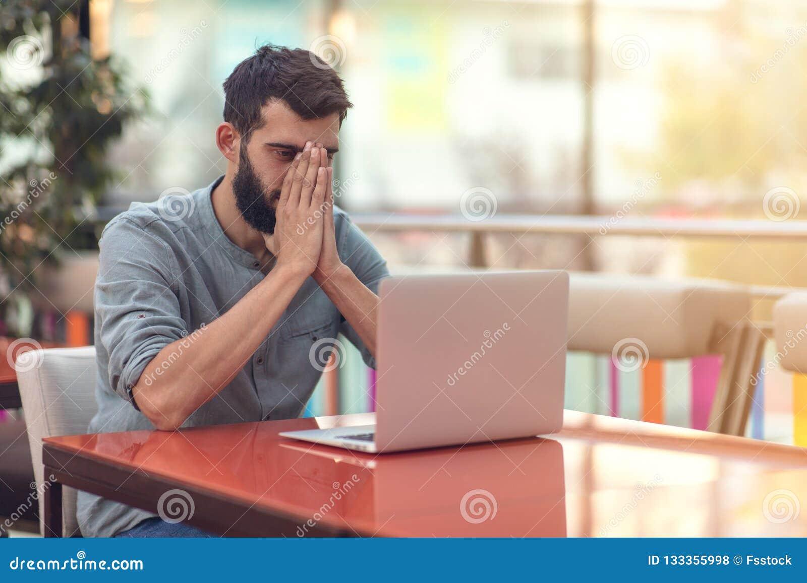 Portrait en buste du concepteur barbu réussi souriant à la caméra tout en travaillant à indépendant au netbook