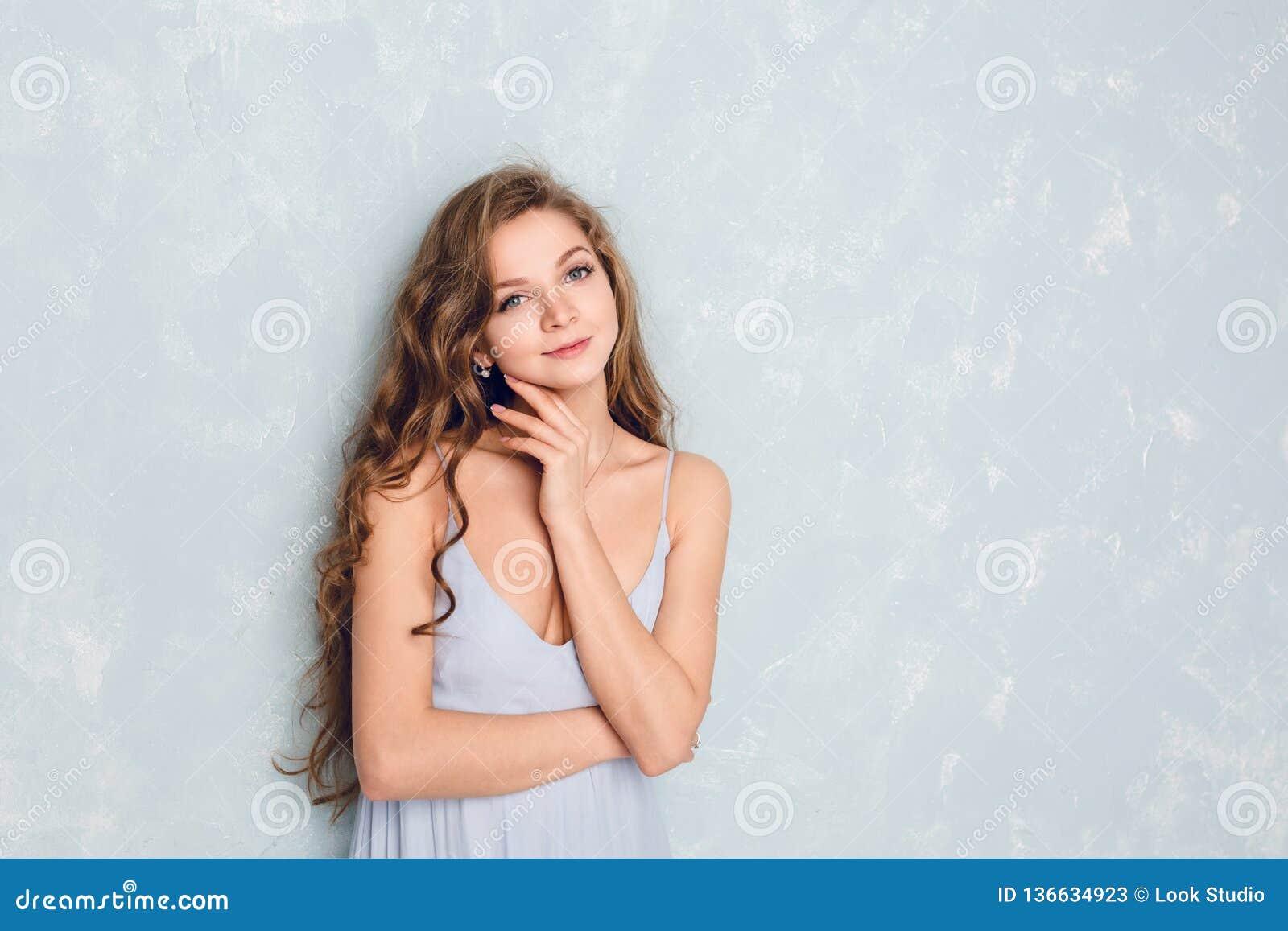 Portrait en gros plan d une belle fille blonde avec les cheveux bouclés se tenant dans un studio Elle porte la robe bleue en soie